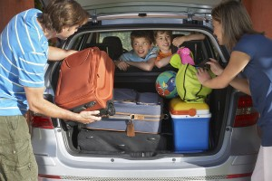 Two young sons watching parents load luggage in car trunk