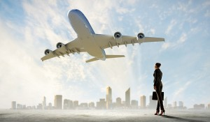 Image of business woman holding suitcase looking at airplane in