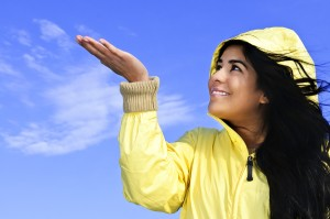Portrait of beautiful smiling girl wearing yellow raincoat looki