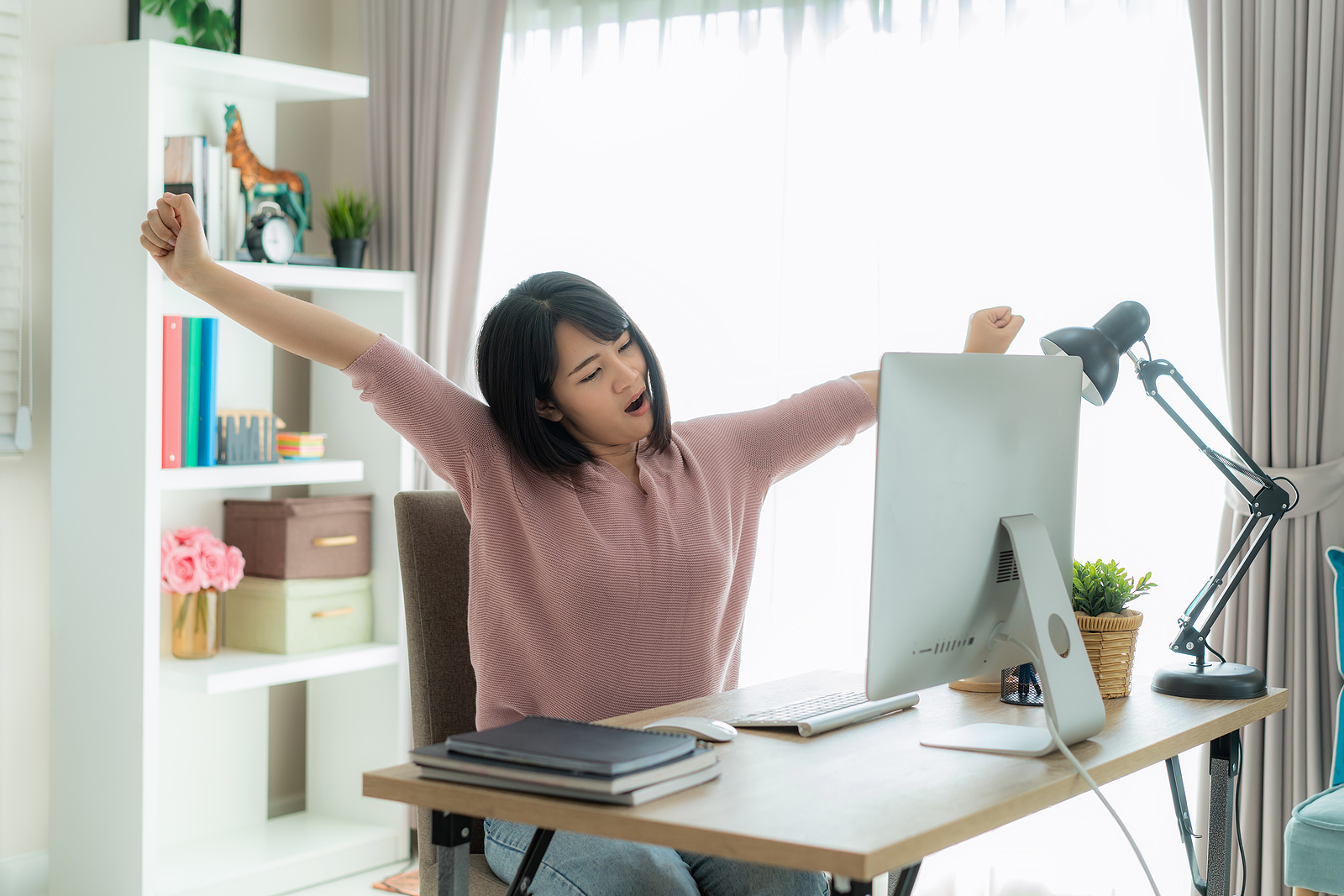 Asian business woman work from home and stretching her body because feel tired and sleepyafter working on computer, smart female working at home. Lifestyle woman relax after working at home concept.